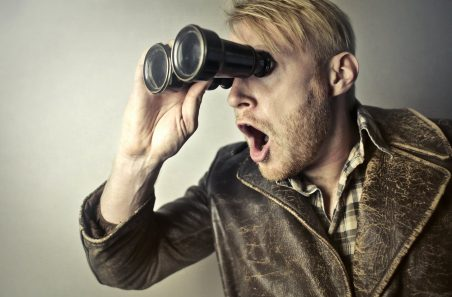 man in brown leather jacket using binoculars